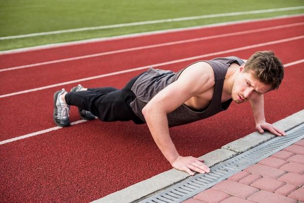 Ein männlicher sportler, der liegestütz auf roter rennstrecke tut