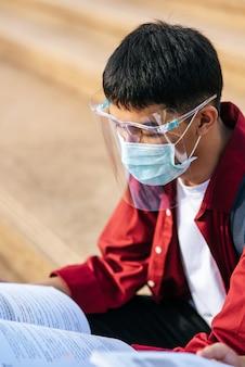 Ein männlicher student, der eine maske trägt und beim lesen sitzt.