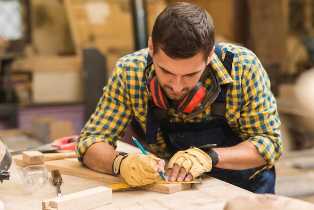 Ein männlicher tischler, der das maß des holzklotzes auf werktisch nimmt