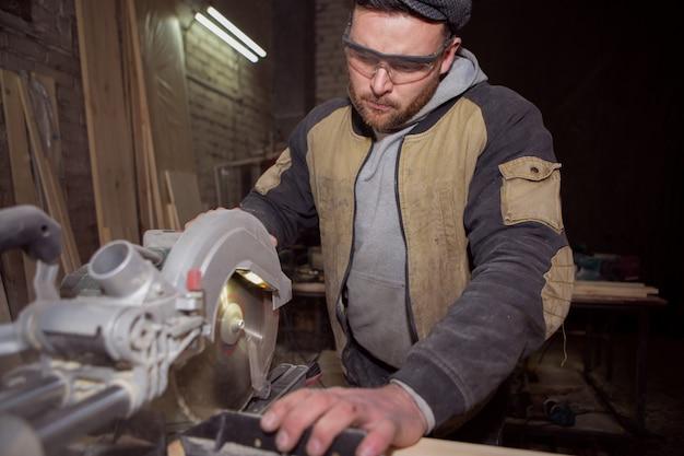 Ein männlicher tischler konzentriert sich in der produktion auf die arbeit mit einer kreissäge