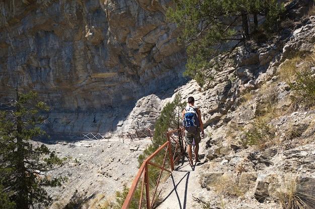 Ein männlicher tourist mit einem rucksack geht einen pfad in den bergen entlang. reisen, trekking,
