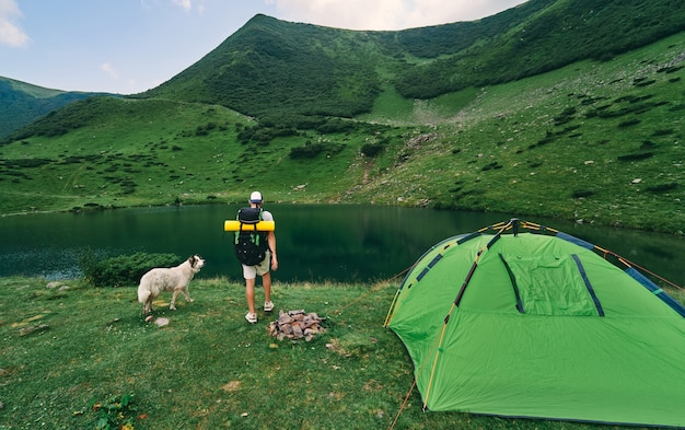 Ein männlicher tourist mit rucksack und gummimatte steht in der nähe eines zeltes am see. junger wanderer mit hund am fuße der grünen berge. reisen, urlaub, tourismus.