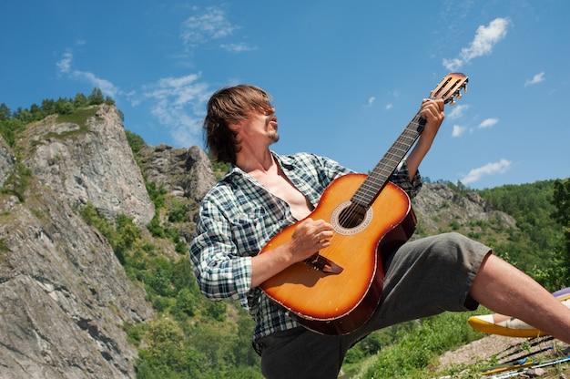 Ein männlicher tourist spielt eine rockrolle auf einer gitarre mit blick auf die berge. genuss der erholung im freien