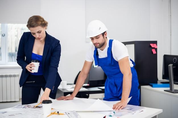 Ein männlicher und ein weiblicher bauingenieur, die im büro an einigen technischen zeichnungen arbeiten