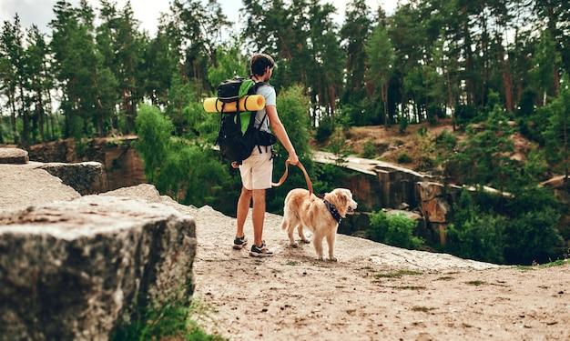 Ein männlicher wanderer mit rucksack und labrador-hund steht auf einem felsigen gipfel und blickt auf den fluss und den wald. camping, reisen, wandern.