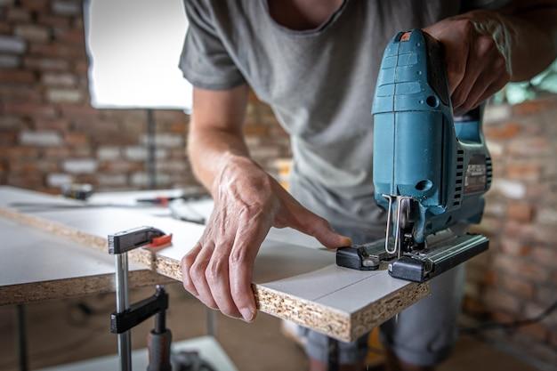 Ein männlicher zimmermann schneidet ein holz mit einer elektrischen stichsäge und arbeitet mit einem baum.