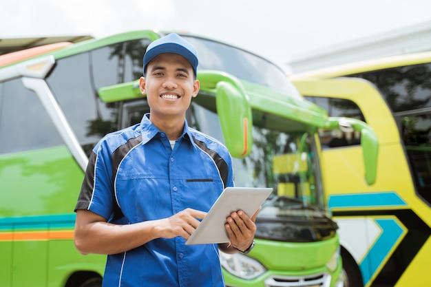 Ein männliches buspersonal in uniform und hut lächelt in die kamera, während es ein pad vor dem hintergrund der busflotte benutzt