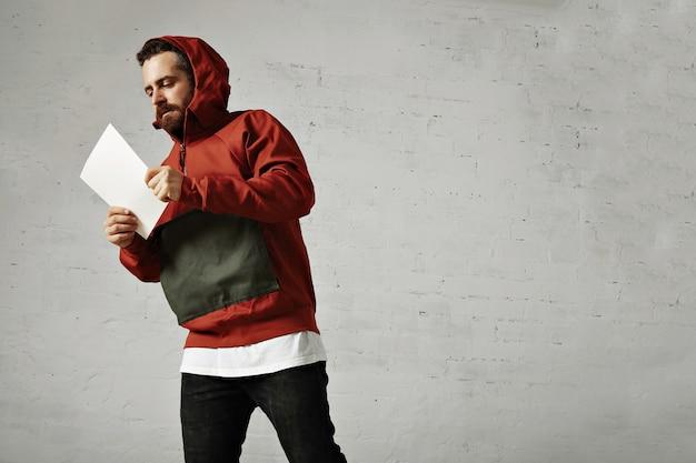 Ein männliches modell in jeans, weißem t-shirt und rotem und grauem parka, das etwas auf weißem leerem blatt papier liest, das auf weiß isoliert wird
