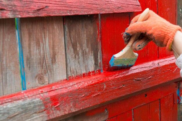 Ein maler handbemalt holzzaun mit roter farbe