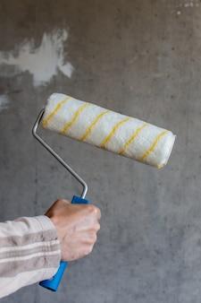 Ein maler malt eine betonwand, eine männliche hand mit einer farbrolle zum streichen einer wand