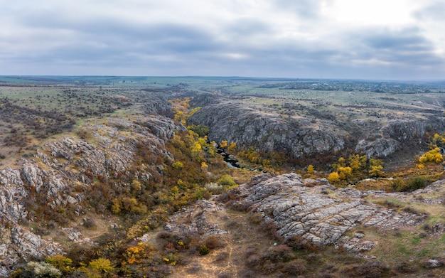 Ein malerischer bach fließt in der aktovsky-schlucht, umgeben von herbstbäumen und großen felsbrocken
