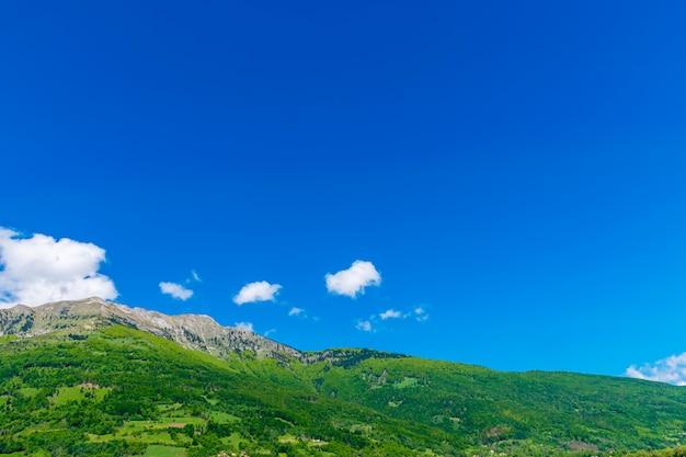 Ein malerischer berggipfel gegen einen blauen himmel mit weißen wolken.