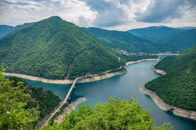Ein malerischer türkisfarbener see kann von der spitze eines hohen berges aus gesehen werden.