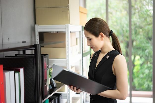 Ein manager steht neben regalen im büro. sie trägt einen schwarzen anzug und hält einen ordner.