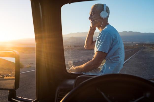 Ein mann allein, der musik mit seinen kopfhörern auf seinem auto hört und den wunderschönen landschaftssonnenuntergang betrachtet - fröhlicher, fröhlicher teenager, der in seinem urlaub unterwegs ist und sein telefon benutzt