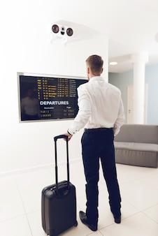 Ein mann am flughafen sieht sich den zeitplan an.