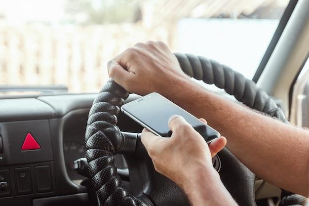 Ein mann am steuer hält einen smartphone in der hand