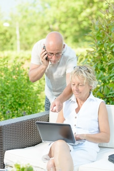 Ein mann am telefon und seine frau am computer