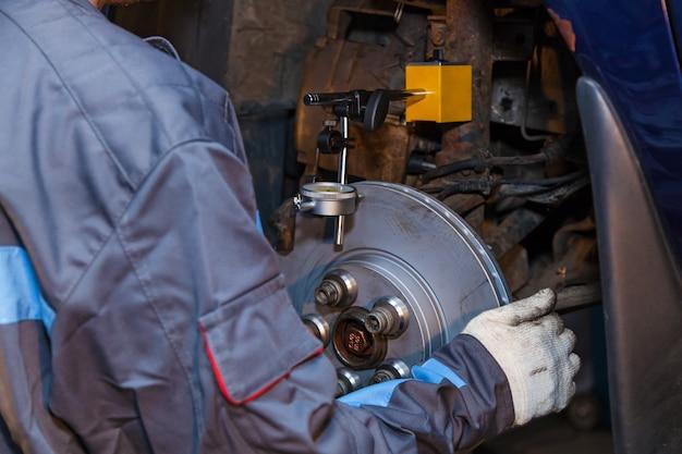 Ein mann arbeitet an einer tankstelle der mechaniker ist damit beschäftigt, das auto zu reparieren