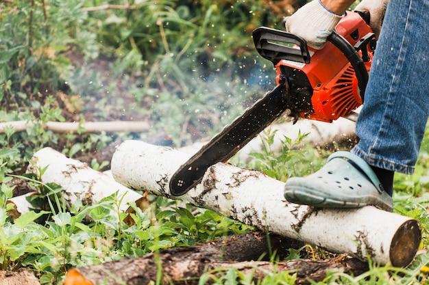 Ein mann arbeitet daran, ein haus zu bauen, holz zu sägen, zu bauen, zu sägen, motorsäge, meißel, nägel, schrauben
