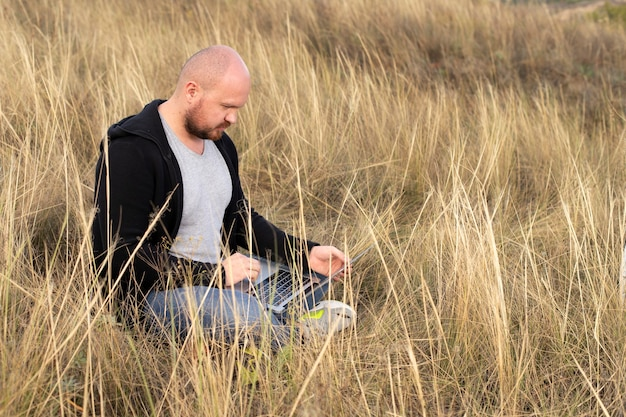 Ein mann arbeitet in der natur an einem computer