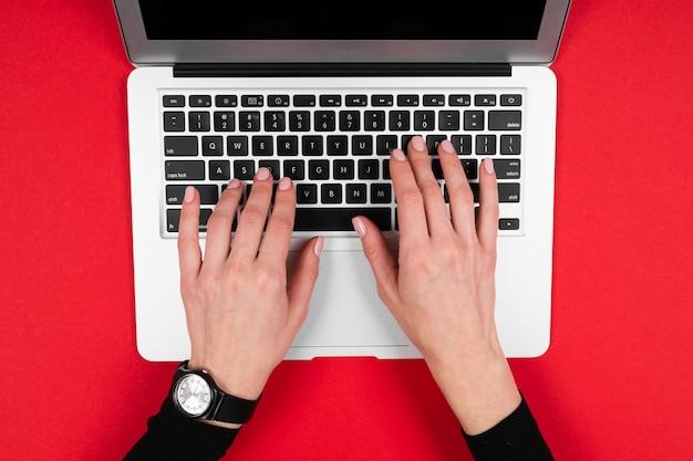 Ein mann arbeitet mit einem laptop, der auf rot isoliert ist