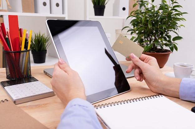 Ein mann arbeitet mit einem tablet und macht auf seinem desktop notizen mit taschenrechner, stiften, bleistiften, karte, telefon und einer anlage im büro