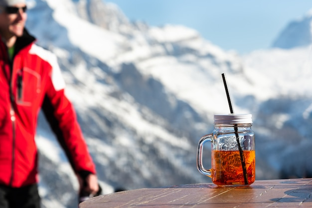 Ein mann auf dem hintergrund der berge geht zu dem tisch, auf dem ein becher aperol steht.