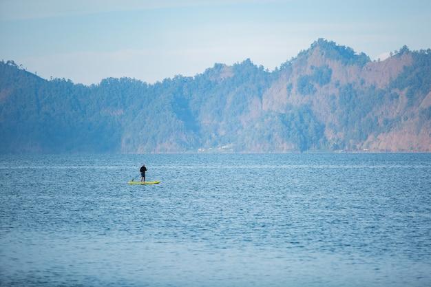 Ein mann auf dem see reitet auf einem sup board.