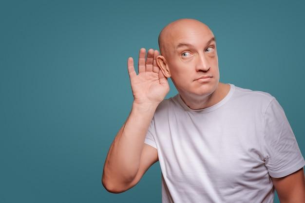 Ein mann auf einem blauen hintergrund, wenn er seine hände in der nähe seines ohrs hält und zuhört