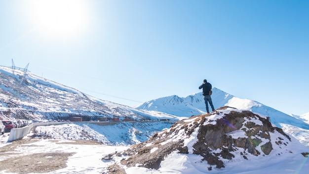 Ein mann auf schnee mit einer kappe bedeckten berg