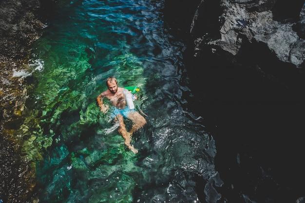 Ein mann auf see sammelt plastikmüll, der sich im wasser befindet