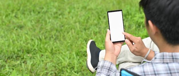 Ein mann benutzt ein weißes smartphone mit leerem bildschirm, während er über der wiese als hintergrund sitzt.