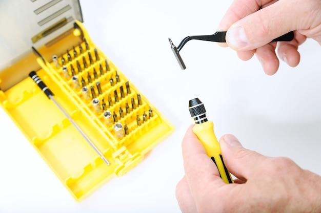 Ein mann benutzt eine pinzette, um etwas in einen schraubenzieher zu stecken.