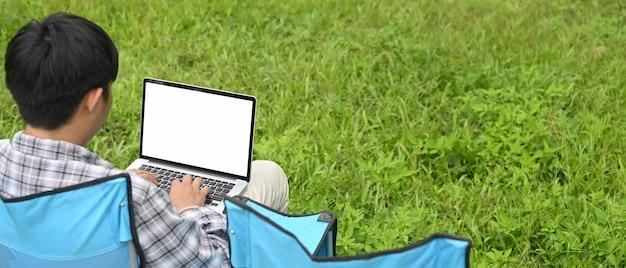 Ein mann benutzt einen computer-laptop, während er über dem park als hintergrund sitzt.