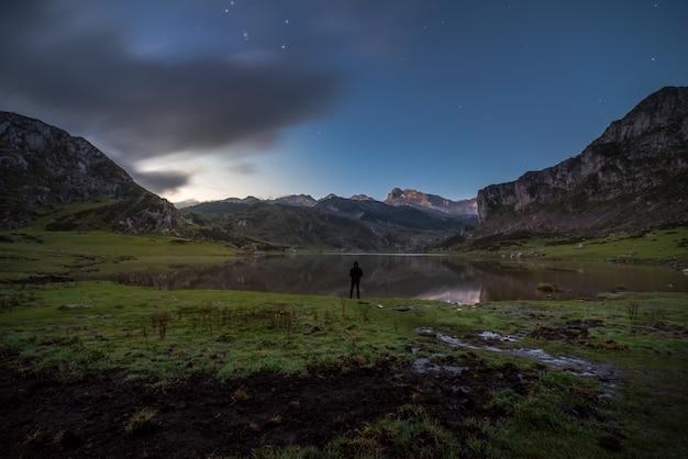 Ein mann beobachtet den see der berge von asturien, spanien