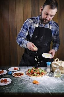 Ein mann bereitet eine pizza vor, knetet den teig und legt zutaten hinein
