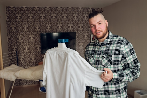 Ein mann bringt ordnung, hält den kleiderdampfer in der hand und glättet die jacke nach dem waschen