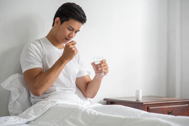 Ein mann, dem es auf der couch nicht gut geht und der antibiotika einnehmen will.