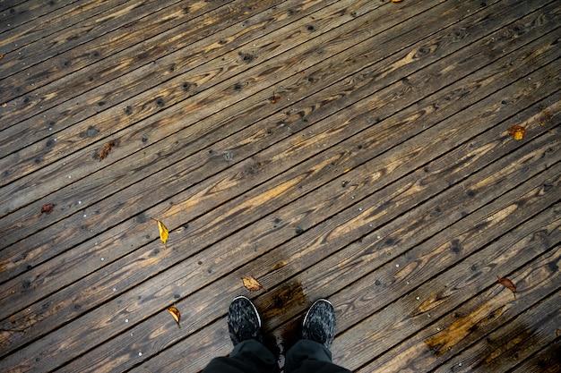 Ein mann, der auf dem alten bretterboden am rainny tag steht