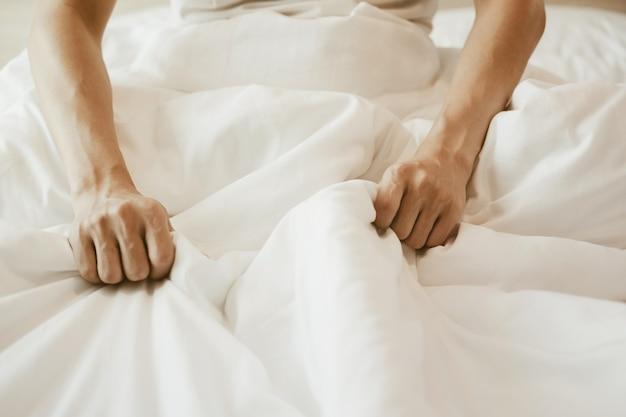 Ein mann, der auf dem bett sitzt und eine weiße decke auf der hand hält. schlafzimmer mit weißem bett und sonnenlicht.