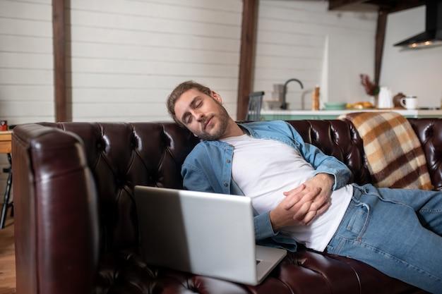 Ein mann, der auf dem sofa schläft, während er fern arbeitet