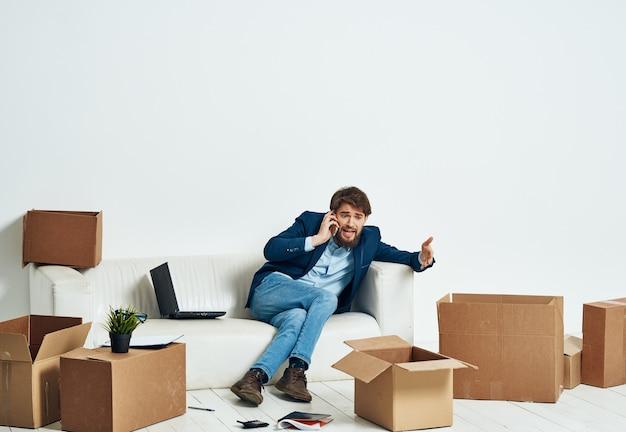 Ein mann, der auf der couch sitzt und am telefon eine offizielle schachtel mit dingen spricht