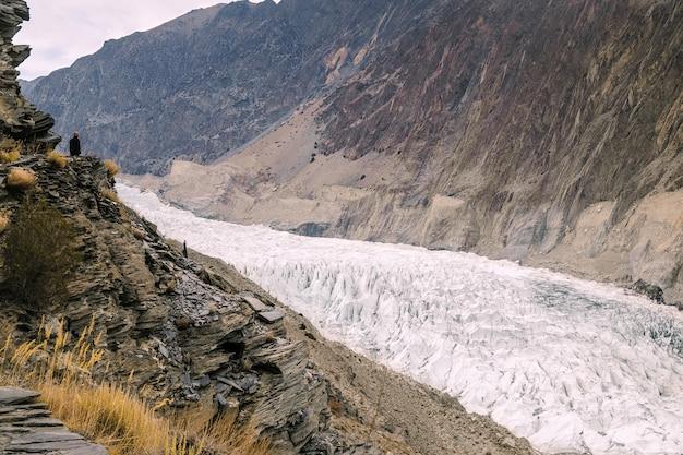 Ein mann, der auf der klippe steht und den passu-gletscher betrachtet. pakistan.