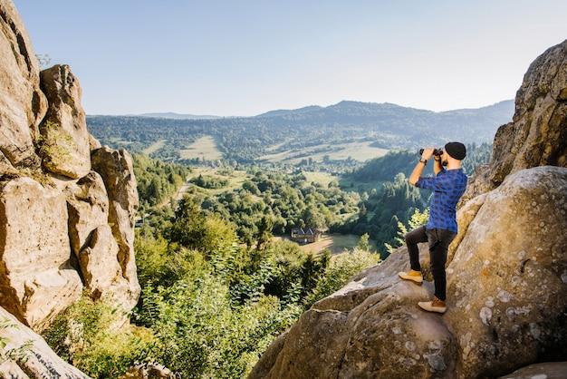 Ein mann, der auf der spitze eines berges steht und in das fernglas am horizont schaut