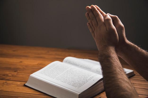 Ein mann, der auf einem buch auf einer dunklen oberfläche betet