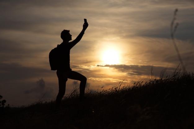 Ein mann, der auf einem hügel steht, der verbindung auf dem hintergrund eines schönen sonnenuntergangs sucht