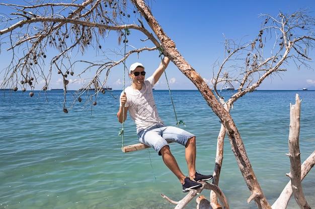 Ein mann, der auf einer schaukel sitzt, auf einem umgestürzten baum am ufer und frachtschiffen am horizont. der stadtrand von gelendzhik. russland, schwarzmeerküste
