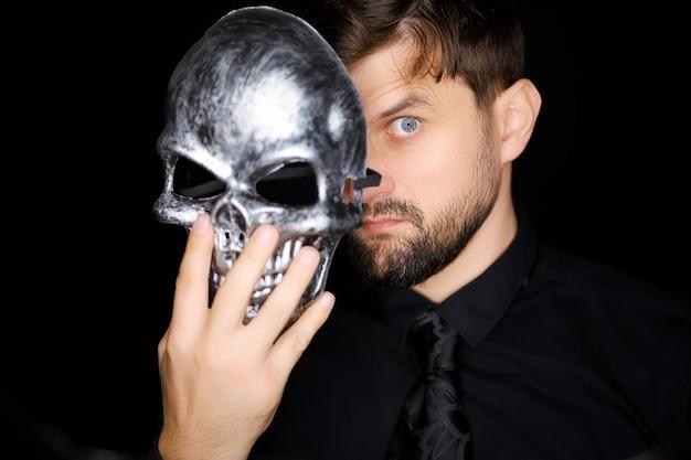 Ein mann, der auf schwarzem hintergrund steht, schaut unter einer skelettmaske hervor, die er sich aufsetzen möchte