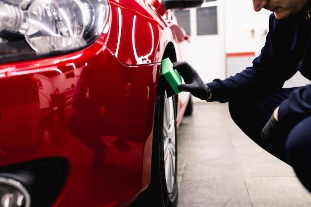 Ein mann, der auto mit schwamm, auto-detaillierungs- (oder reinigungs-) konzept säubert. selektiver fokus.